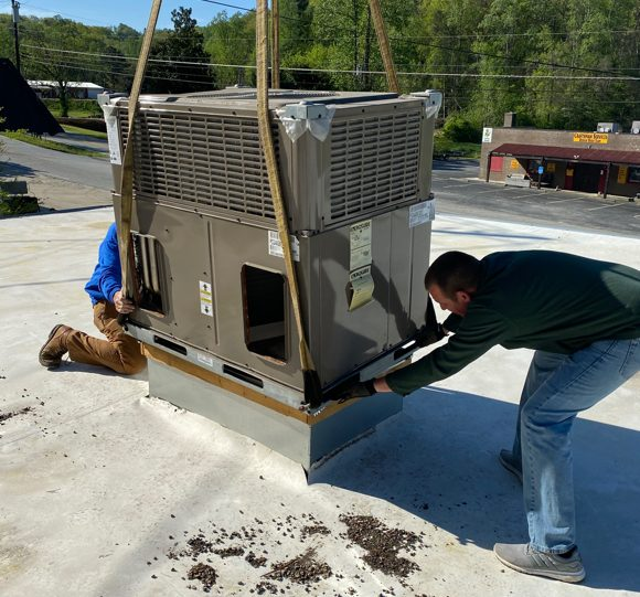 Two Blue Ridge Heat and Cooling HVAC Technicians Install An A/C Unit With A Crane On A Roof Top